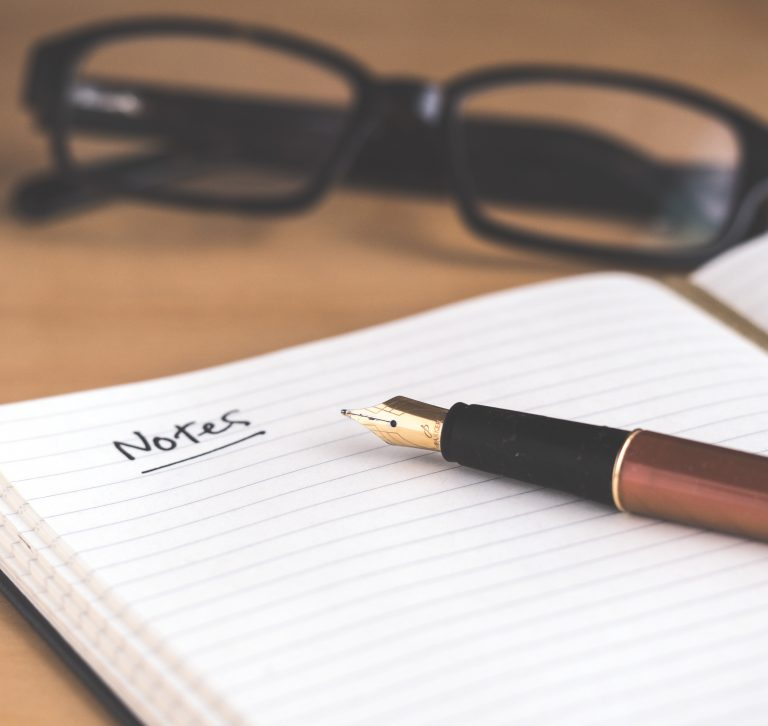notebook on the desk next to a pencil and a pair of glasses